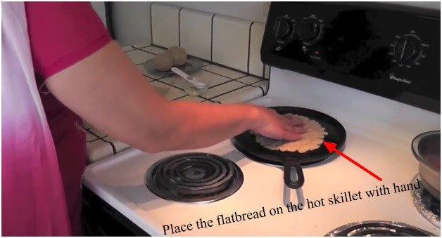 Place the flatbread on the hot skillet with hand